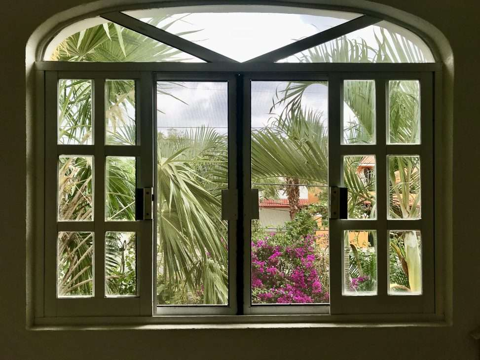 Large windows overlooking lush tropical gardens from the villa