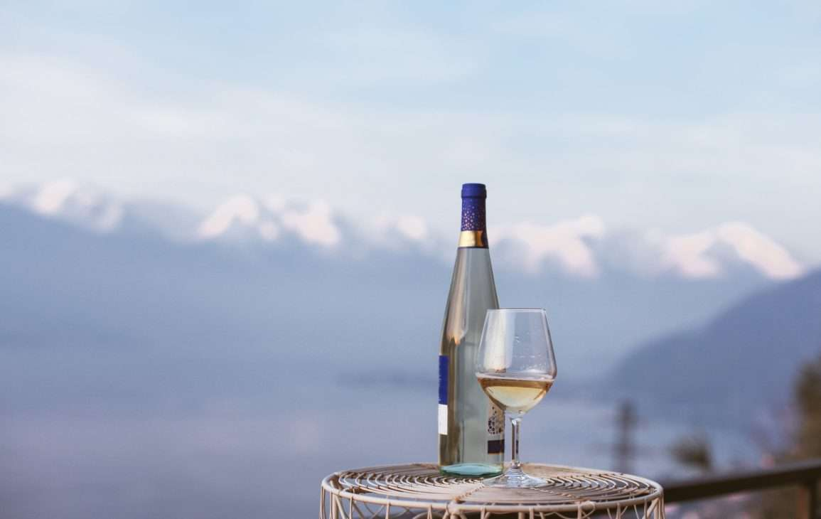 Wine bottle and glass in front of snow-capped mountains