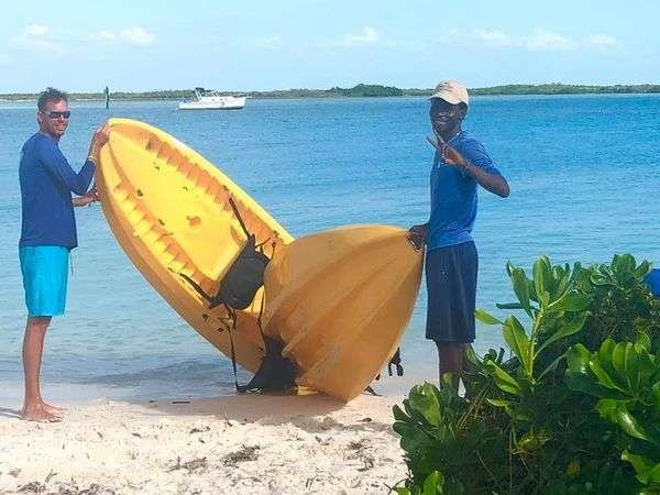 Two kayak guides holding a yellow kayak